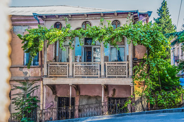 Old ornate grungy house in Tbilisi Georgia covered with grape vines