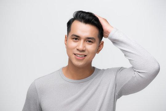 Asian man looking at his hair in mirror