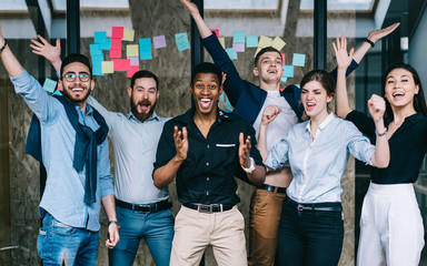 Young crew of happy excited male and female business partners celebrating completed startup project while looking at camera and laughing, overjoyed colleagues feeling amazed of done good work