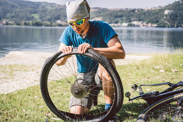 Bike Repair. Man Repairing Mountain Bike. Cyclist man in trouble rear wheel wheel case of accident. Man Fixes Bike near lake in Italy background mountains. cyclist repairing bicycle wheel outdoors Wall mural