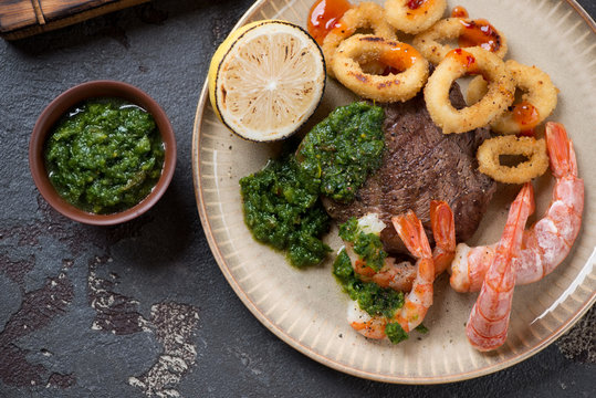Surf and turf or marbled beef steak, shrimps and calamari rings with chimichurri sauce, closeup, top view
