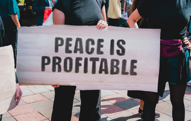 "The phrase "" Peace is Profitable "" drawn on a carton banner. A girl holds a cardboard with an inscription. Girls on the street. War. Conflict. Politics"