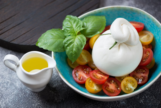 Burrata cheese with cherry tomatoes and fresh green basil in a turquoise bowl, studio shot over light-grey stone background