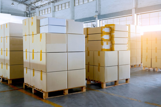 Stack of cardboard boxes on wooden pallets. Large shipments goods at interior warehouse storage. Cargo export. Warehouse industry shipping logisics.