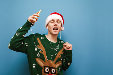 Cheerful Christmas guy dancing in headphones and with smartphone in his hand against a blue background, listening to music with his eyes closed, wearing a santa hat and a warm sweater. Isolated.