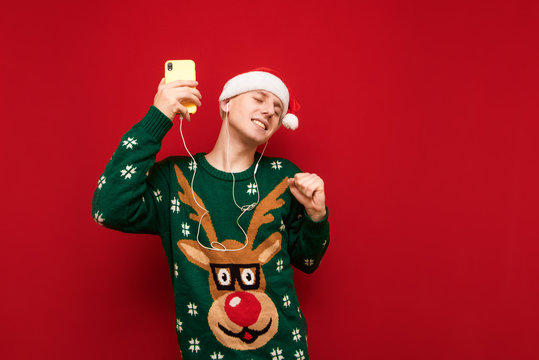 Happy young man listening to music and dancing with smartphone in hand on red background, wearing Christmas hat and sweater, guy having fun. Christmas mood concept.