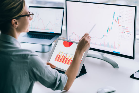 Crop businesswoman researching charts on computer