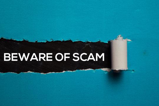 Beware Of Scam Text written in torn paper