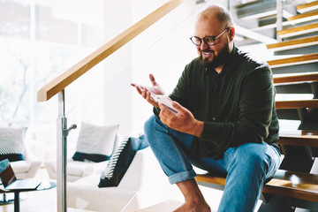 Cheerful bearded blogger in eyewear watching online lifestream on smartphone via home wifi sitting on wooden stairs in apartment.Positive young man laughing funny news on internet website on cellular