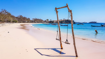 A swing placed on the seashore of Pink Beach, Lombok, Indonesia. The swing has very simple wood construction. Waves gently wash the pillars of it. In the back there are few boats anchored in the bay.