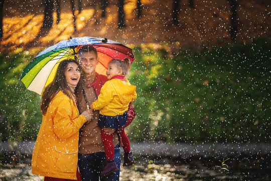 Happy funny family with colourful umbrella under the autumn rain.