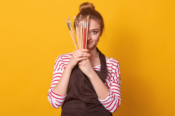 Picture of delighted tender cute young lady holding lots of brushes in both hands, covering half of face with art equipment, wearing striped sweatshirt and brown apron. People and free time concept.