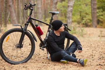 Outdoor picture of athletic strong sportsman wearing black shirt, sport pants, hat and trainers, leaning on bicycle, looking far ahead, having training around nature. Nature and people concept.