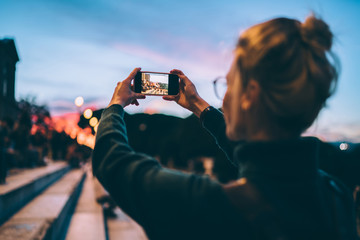 Back view of hipster girl taking pictures of evening city via smartphone application connected to 4g for using cellular online app, female generation photographing landscape during sightseeing