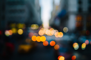 Evening defocused view with bokeh lights of urban setting and moving cars on road in city district,blurred background of transportation in Metropolis downtown with copy space for advertise information