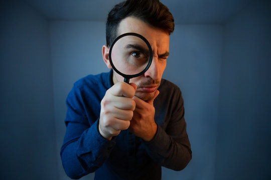 Surprised Young man student holding magnifying glass looking to camera with a pensive emotion isolated over grey  background. Science and curiosity concept.