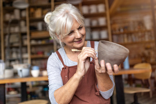 Senior woman pottery artist makes ceramics from clay