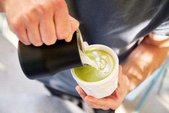 Male barista making vegan matcha cappuccino with oat milk
