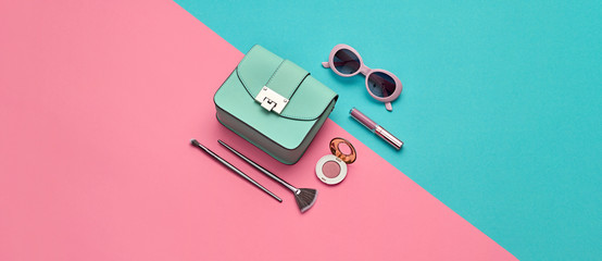 Fashion party girl Flat lay. Minimal. Woman Essentials accessories. Trendy Clutch, sunglasses, cosmetic makeup. Coloful pastel blue pink Set. Creative pop art concept, fashionable color banner