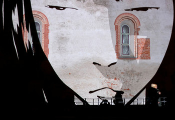 A woman walks past graphic animation 'Mystery of Skarnu Street' during the festival of lights in Riga