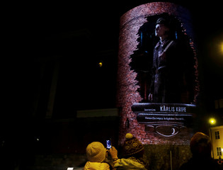 A woman takes a picture of projection 'Centenary of Heroes' during the festival of lights in Riga