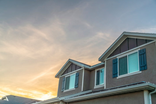 Exterior upper storey of a home with golden cloudy sky background at sunset