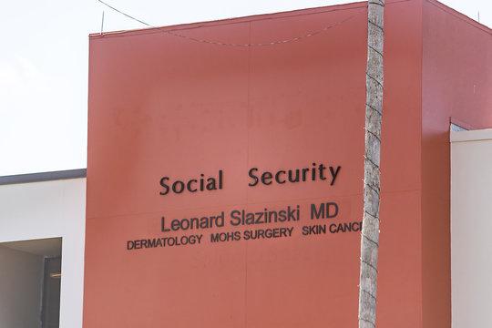 Sarasota, USA - April 28, 2018: Florida city during day with closeup of Social Security building sign and Dermatology, surgery center