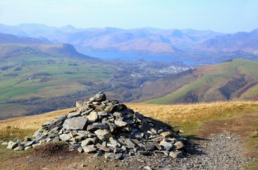 Pile of stones, or cairn, on Blencathra in the English Lake District, with Derwent Water in the distance