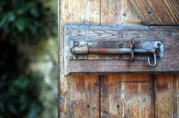 Artistic close up shot of an old iron or steel bolt, on a rustic wooden door