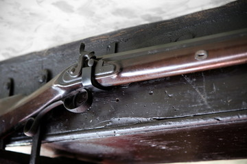 Close up detail of old flintlock rifle or musket, hanging on an old oak beam