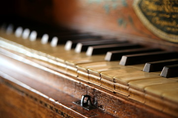 Close up shallow focus shot of a vintage piano or harpsichord keyboard, made of ebony, ivory and hardwood