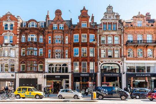 London, UK - September 13, 2018: Neighborhood district of Knightsbridge brick architecture, road, cars in street traffic on sunny day