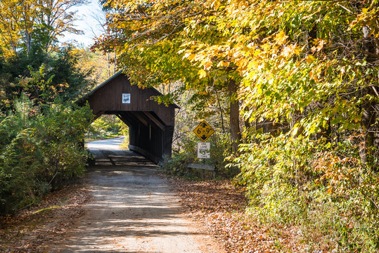 Historic wooden covered bridge along dirt road in the countryside on a sunny autumn day. Colourful autumnal trees line the road. New Hampshire, USA.