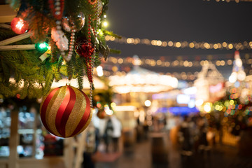 Picture of red with golden Christmas ball on Christmas tree on blurred background in evening.