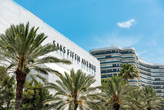 Bal Harbour, USA - May 8, 2018: Bay Harbor in Miami Florida with green palm trees on exterior of condo apartment building by mall for Saks Fifth Avenue shopping center destination