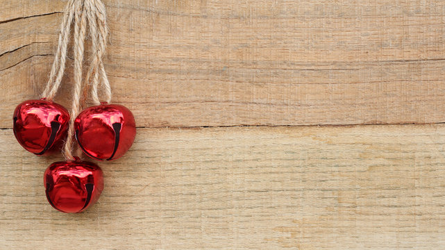 three red jingle bells hanging on rope against a wood background with writing space