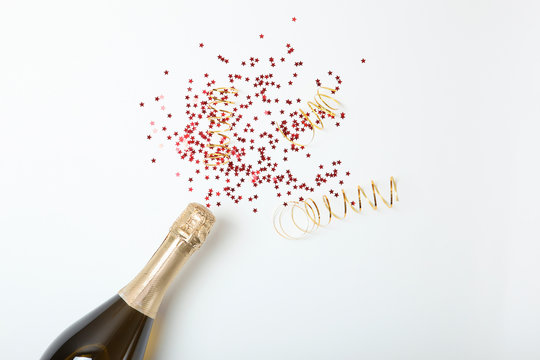 bottle of champagne and confetti on a colored background top view. Concept holiday, celebrate, new year, christmas, birthday.
