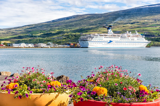 Akureyri, Iceland - June 17, 2018: Fishing village town harbor marina with cruise ship boat and fjord with mountains and flower pots