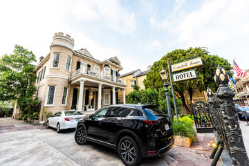 New Orleans, USA - April 23, 2018: Old town Royal street Louisiana famous city and the Cornstalk Fence Hotel with sign by entrance and cars parked