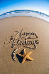 Happy Holidays message written in smooth sand with fisheye effect on starfish and frothy white waves