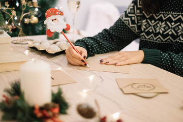 Woman writing Christmas cards with Santa claus pencil