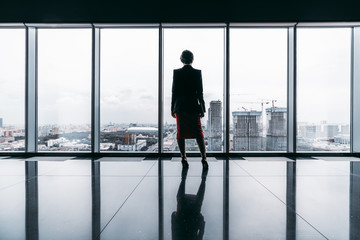 Printed kitchen splashbacks Moscow Rearview of a female entrepreneur on the top of a modern business office skyscraper standing near big panoramic windows and pensively looking at cityscape and construction site; floor with reflections