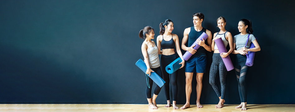 Group of diversity ethnic people holding Yoga mat talking together with smile. Asian girl laughing with funny face after finish training class. Happy and relax time in group of friend in Banner size.