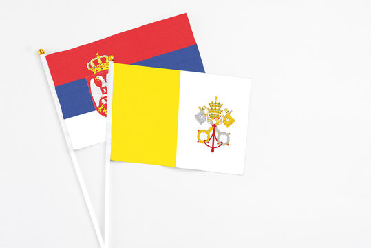 Vatican City and Serbia stick flags on white background. High quality fabric, miniature national flag. Peaceful global concept.White floor for copy space.