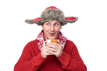 Funny happy man in a red sweater, scarf and winter hat holds in his hands a mug with a hot drink, isolated on white background