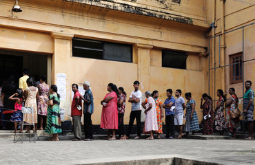 People stand in a line to cast their votes during the presidential election at polling station in Colombo