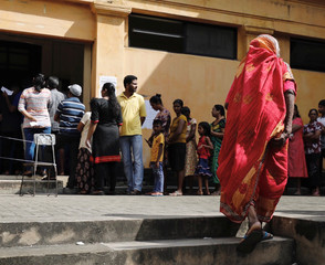 People stand in a line to cast her vote during the presidential election at polling station  in Colombo