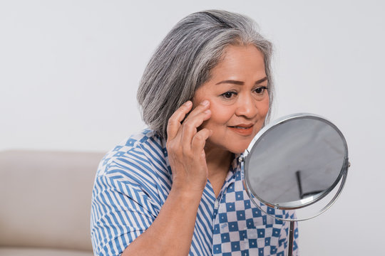 Old woman is looking in the mirror the face wrinkle