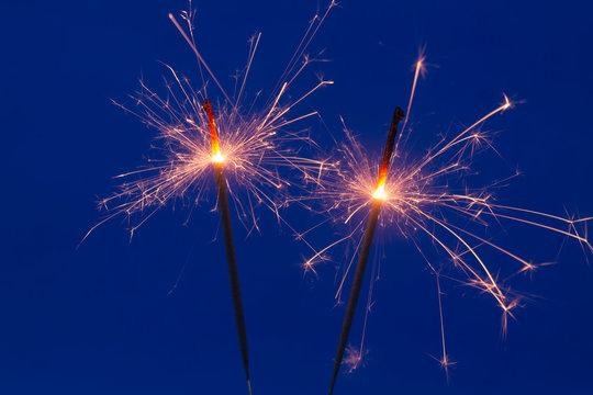 Burning sparklers on blue background