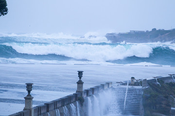 Big waves breaking on the promenade of La Coruña with the buildings of the city and the lighthouse of the Tower of Hercules in the background
